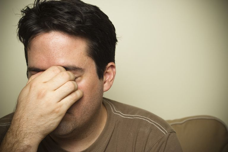 man with sinus pain holding nose