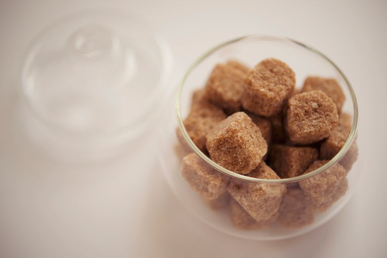 A glass bowl of brown sugar cubes