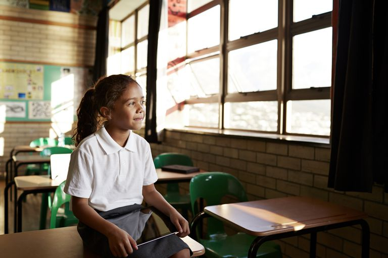Girl looks out of a classroom window.