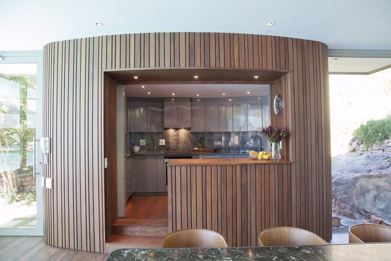 A cylinder pod room houses the kitchen in this modern home