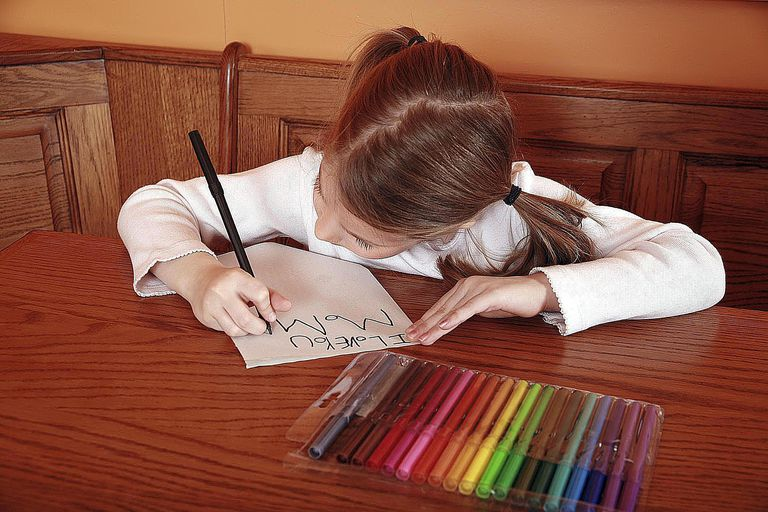 A 5 year old girl making a card for her mother that reads I Love You Mom.