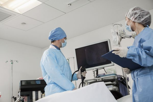 Two surgeons preparing for surgery; patient lying down