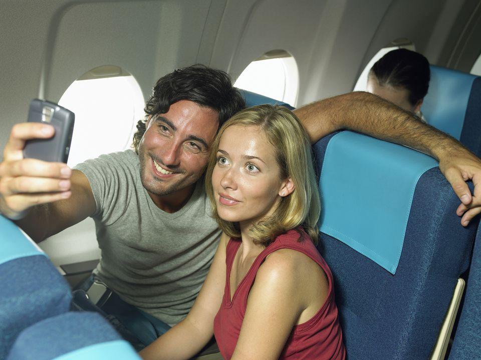 couple on plane taking selfie