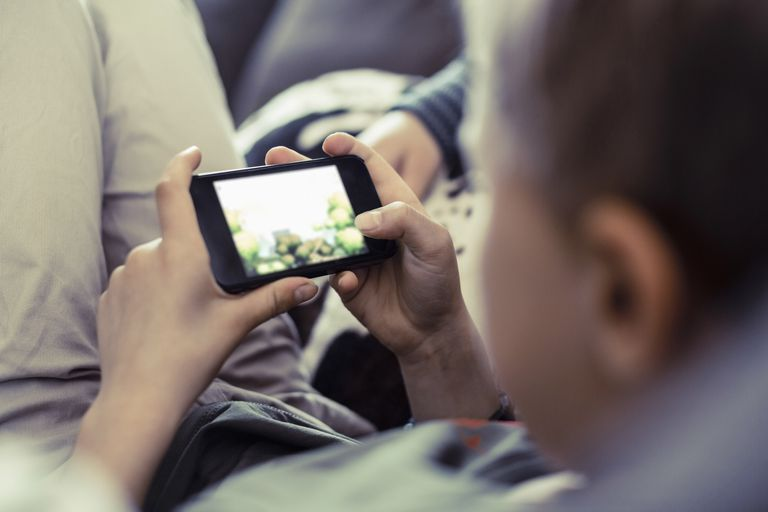 Boy playing game on mobile phone