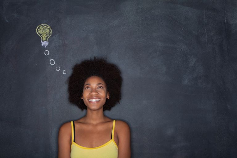 A woman standing in front of a blackboard with a drawn lightbulb pointing towards her head.