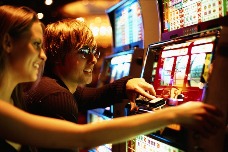 Young couple playing slot machine