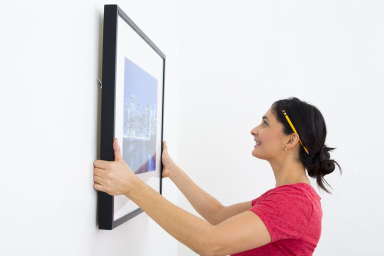 Mixed race woman hanging painting