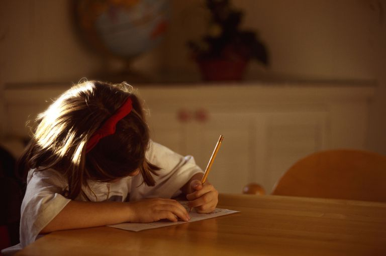 Girl doing homework, sitting at table