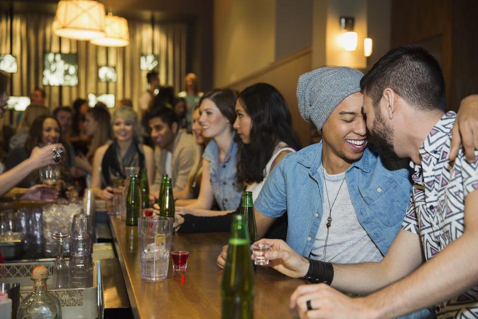 Gay couple hugging and drinking at bar