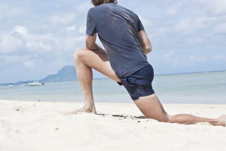 man doing hip flexor stretch on beach