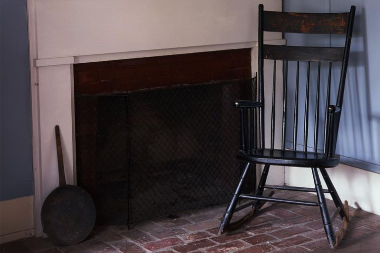 Antique rocking chair at rustic fireplace