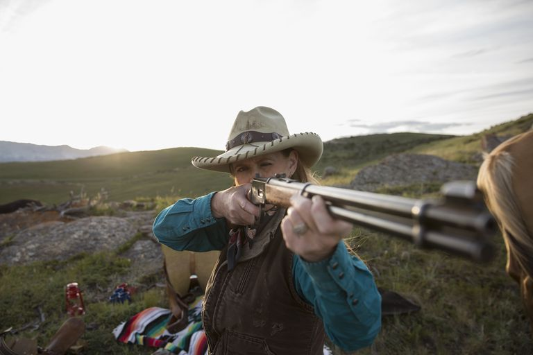 Female rancher aiming rifle in remote field