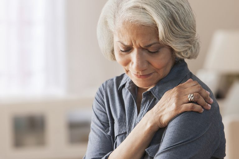 Woman rubbing shoulder in pain