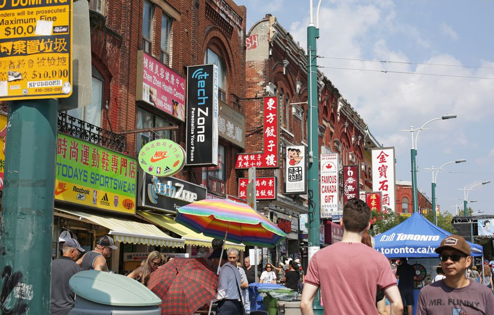 Shopping in Toronto's Chinatown, Spadina Avenue in summer. Colorful signs in the multi-cultural downtown Kensington neighbourhood.