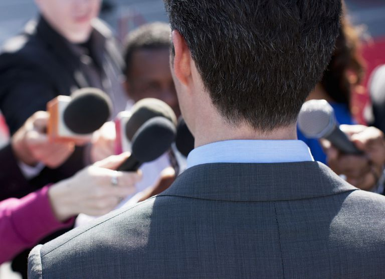 A photo of a man surrounded by TV reporters at a news conference.