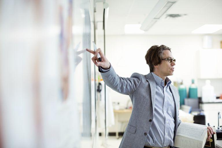 Male professor teaching in college science lab