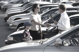 Car salesman shaking hands with woman and son
