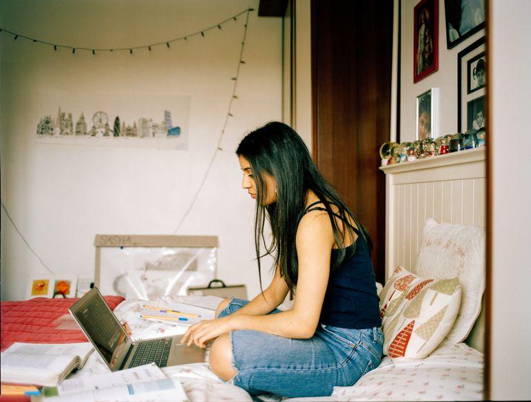 Teenager on laptpo in room