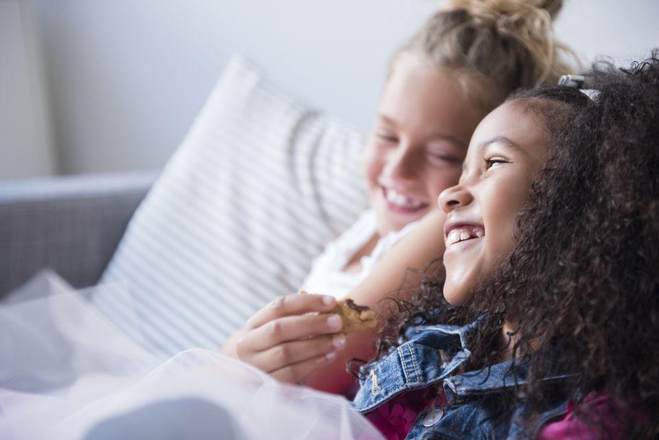 Smiling girls eating cookie on sofa