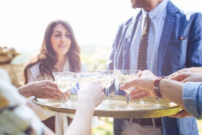 Woman (model) says no to acohol as man offers tray of drinks