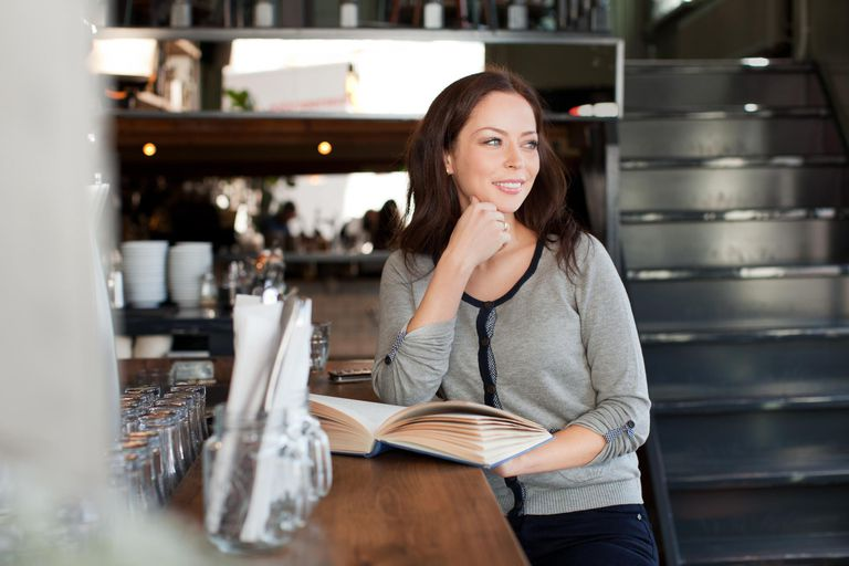 Woman with book in bar