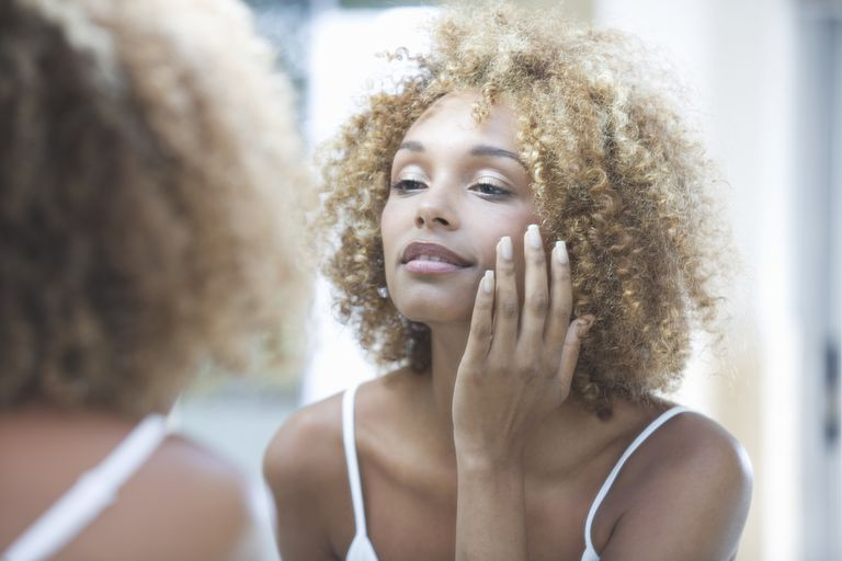woman in mirror looking at face