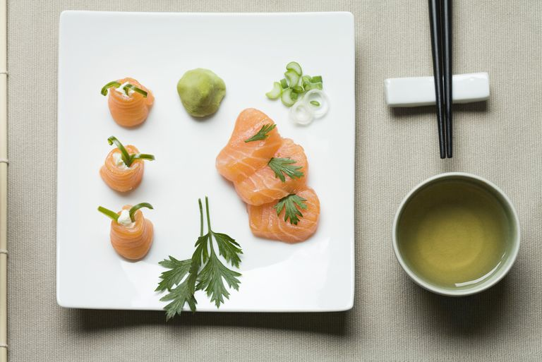 Assorted sushi arranged on large sushi plate with tea and chopsticks alongside
