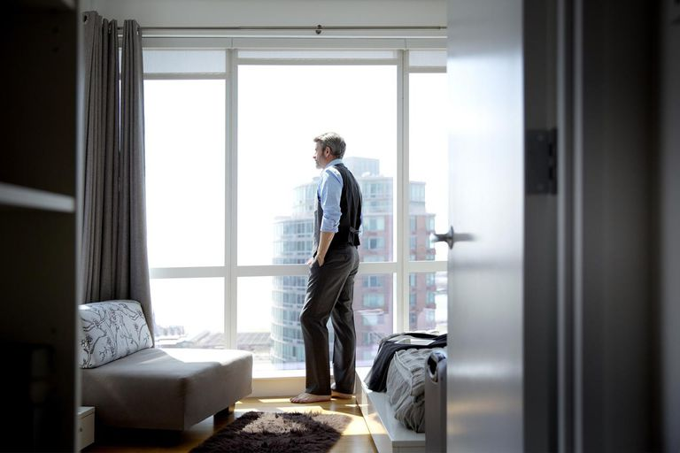 Man Looking Out of Highrise Apartment Window