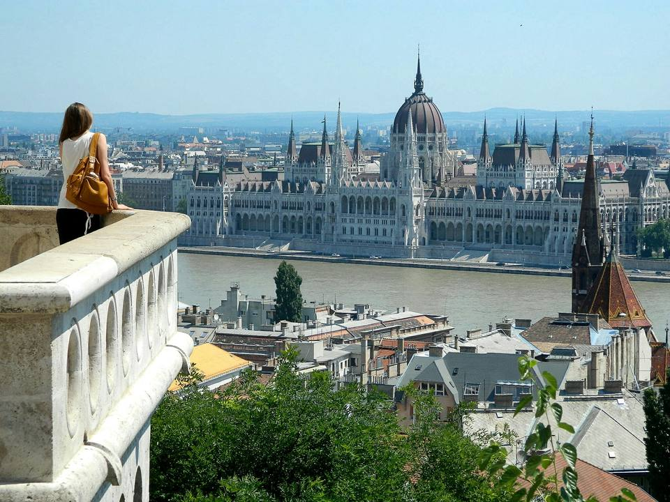 Rear View Of Woman In Balcony Looking At Hungarian Parliament Building