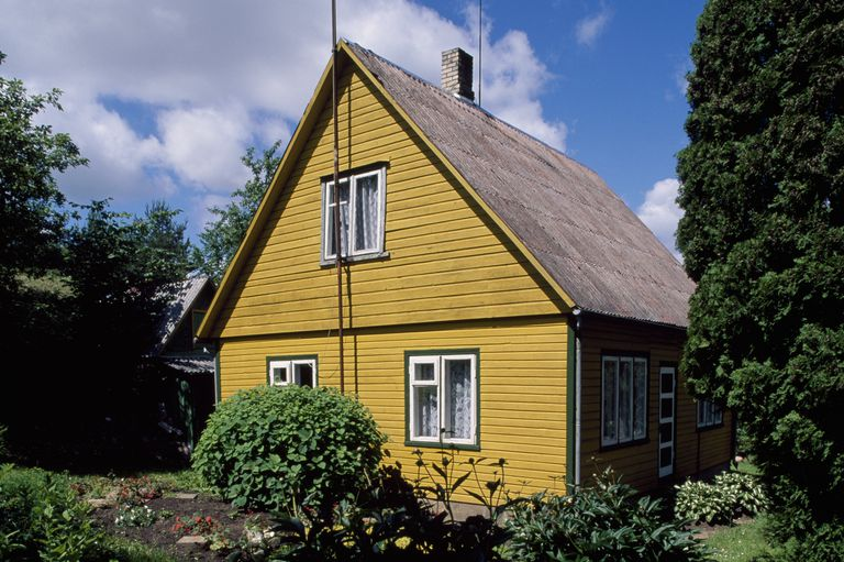 Mustard colored gable side of a house with steep roof