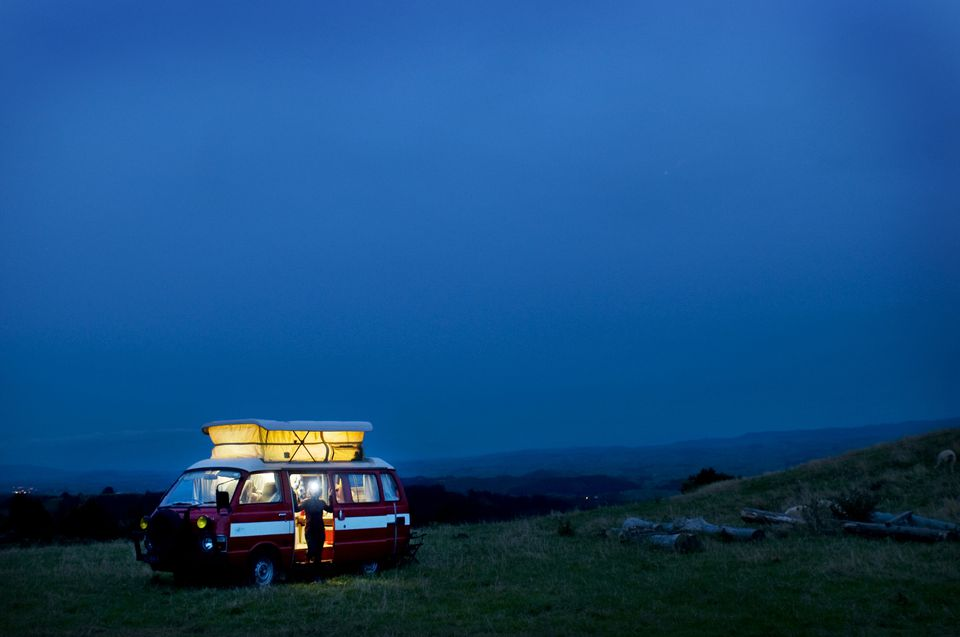 A camper van on a rustic hill at dawn.