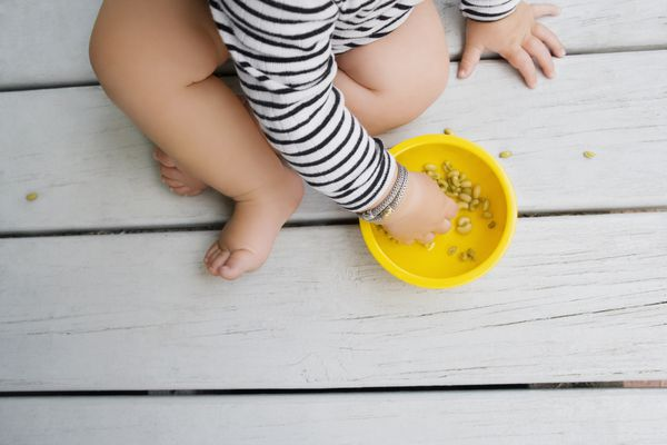Low section view of a baby girl eating cereal