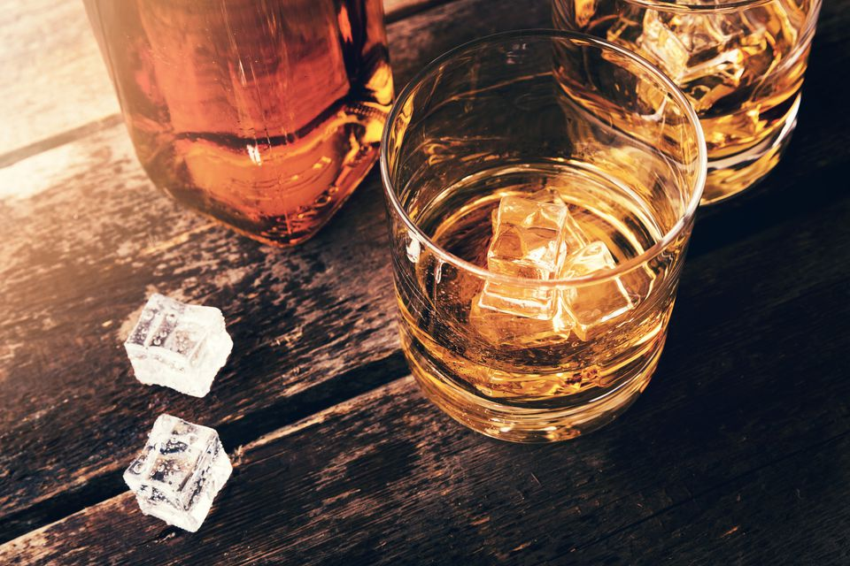 Bottle of whiskey and two glasses of whiskey with ice on a wooden table.