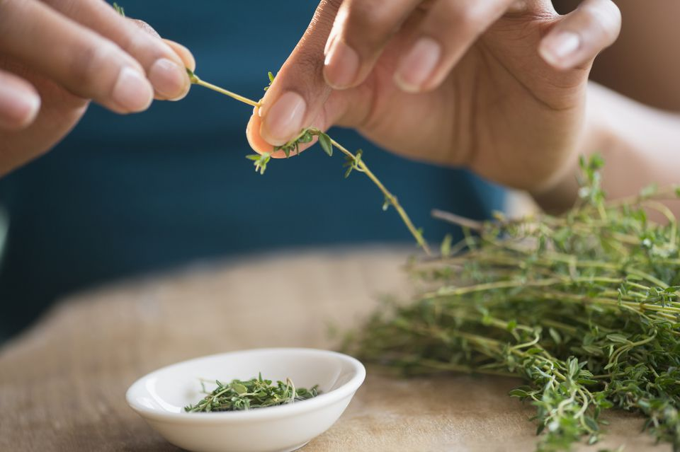 Mixed race woman trimming herbs