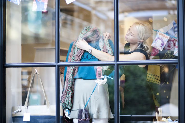 Woman dressing mannequin in storefront window