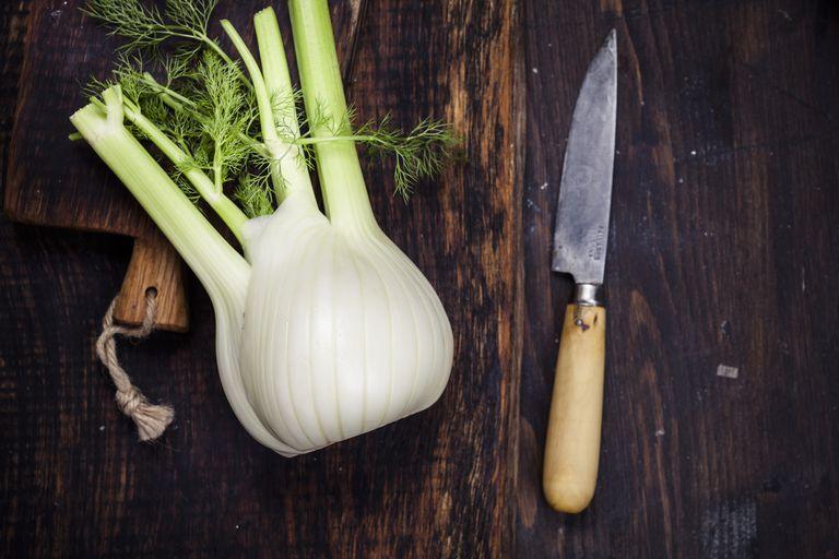 Fennel corm on chopping board, kitchen knife