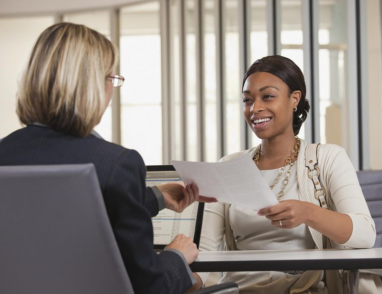 Woman handing resume to interviewer