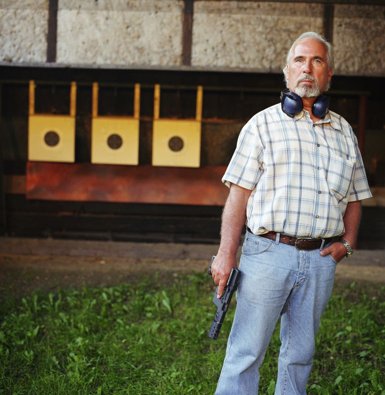 Senior man holding handgun in shooting range, portrait