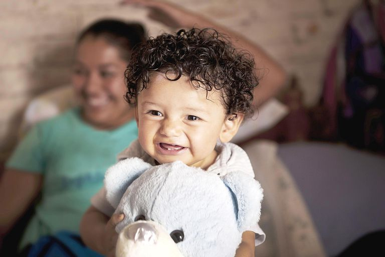 Mexican happy baby holding his teddy bear.