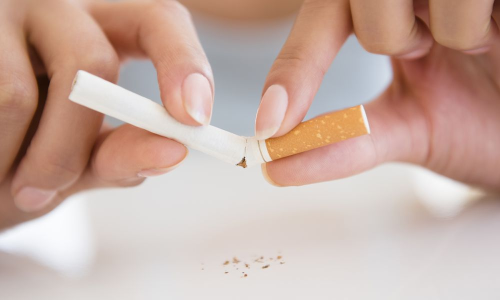 Close up of Hispanic woman breaking cigarette