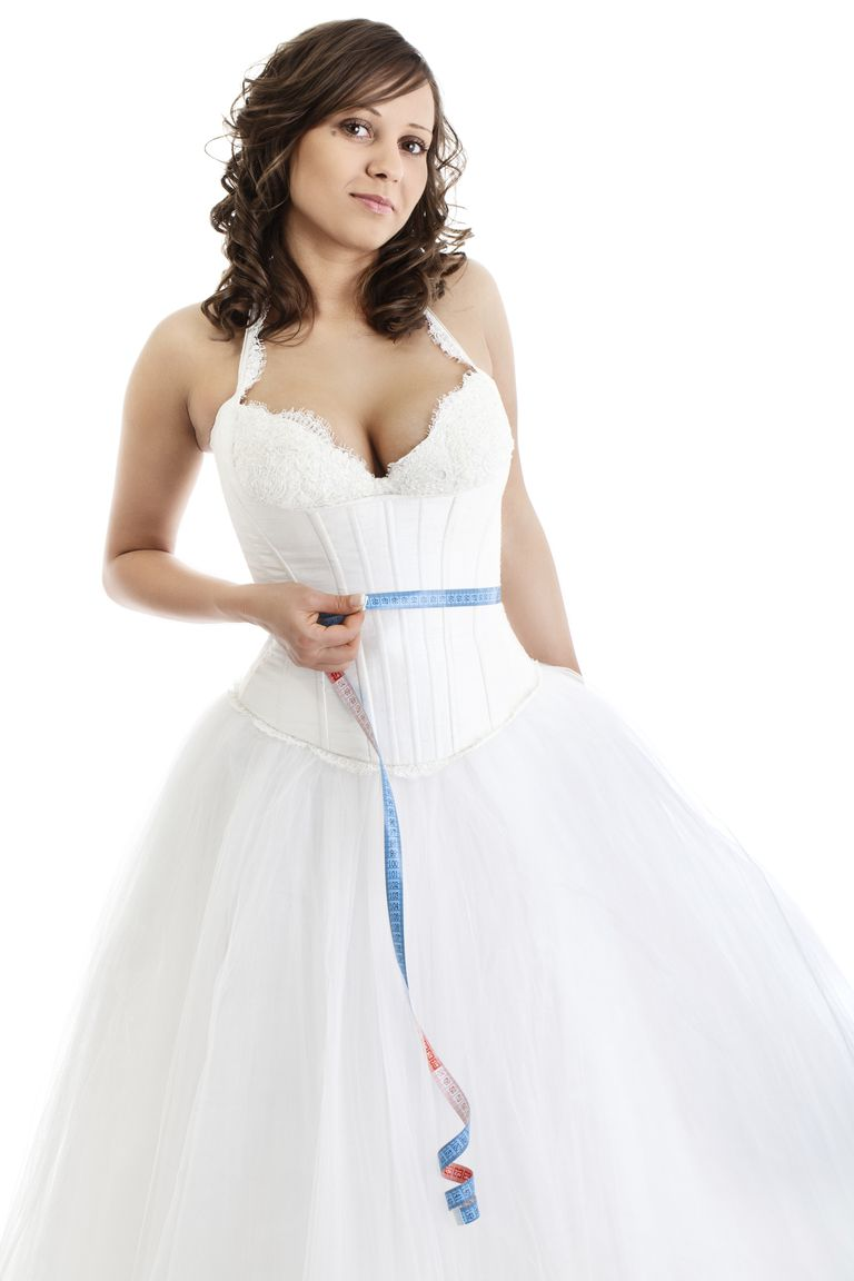 Woman in wedding dress with measuring tape