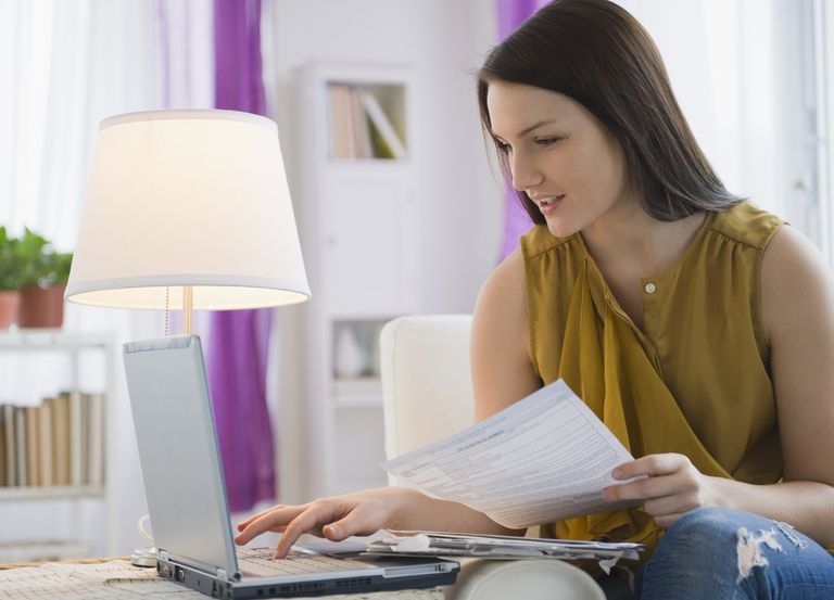 USA, New Jersey, Jersey City, Young woman paying bills on line
