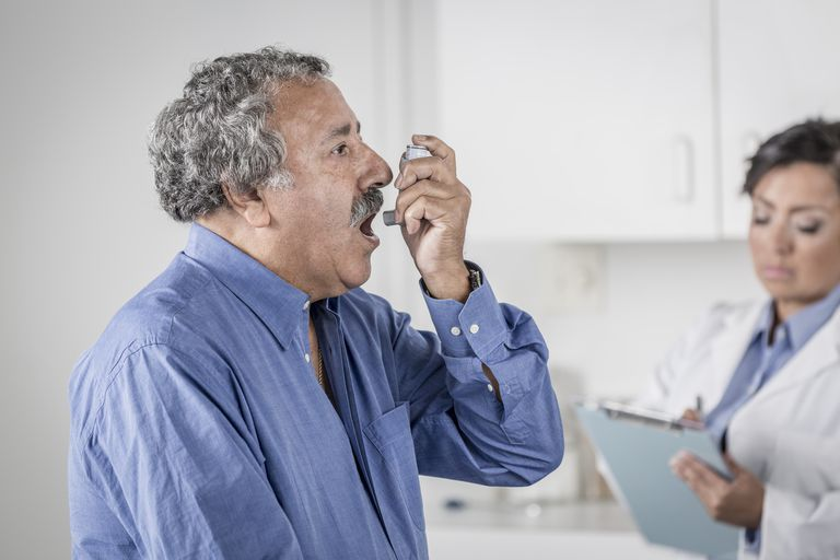 Senior man using asthma inhaler in doctor's office