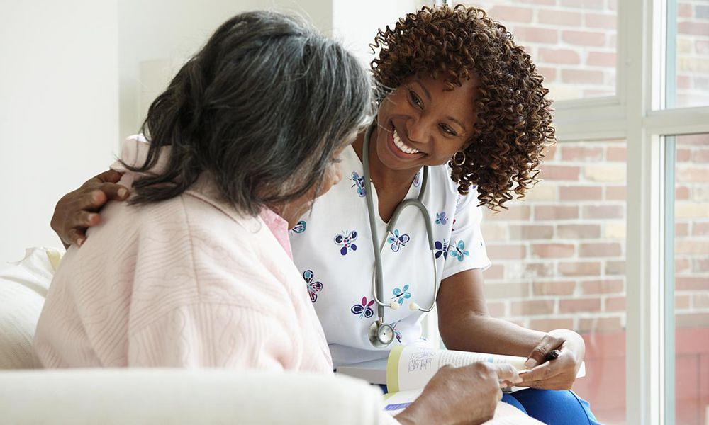 Smiling Nurse Looking At Book With Senior Patient