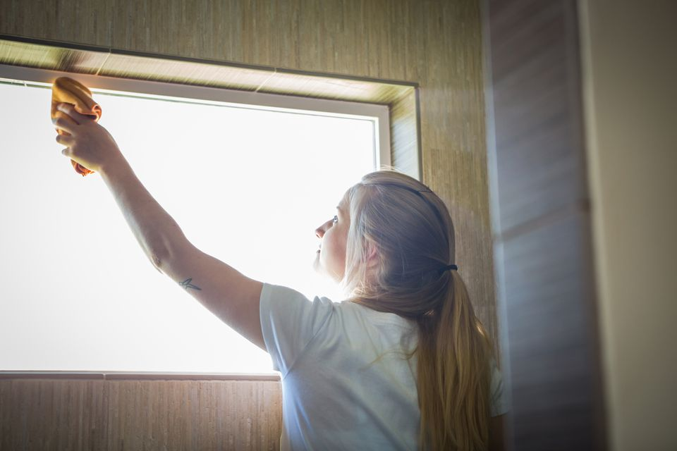 Young woman cleaning window with green cleaning products