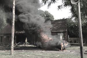 car burning next to house