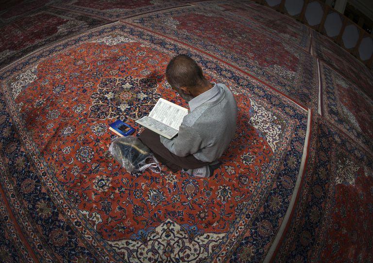Iran, Fars Province, Shiraz, iranian shiite muslim man reading the koran in fatima al-masumeh mosque