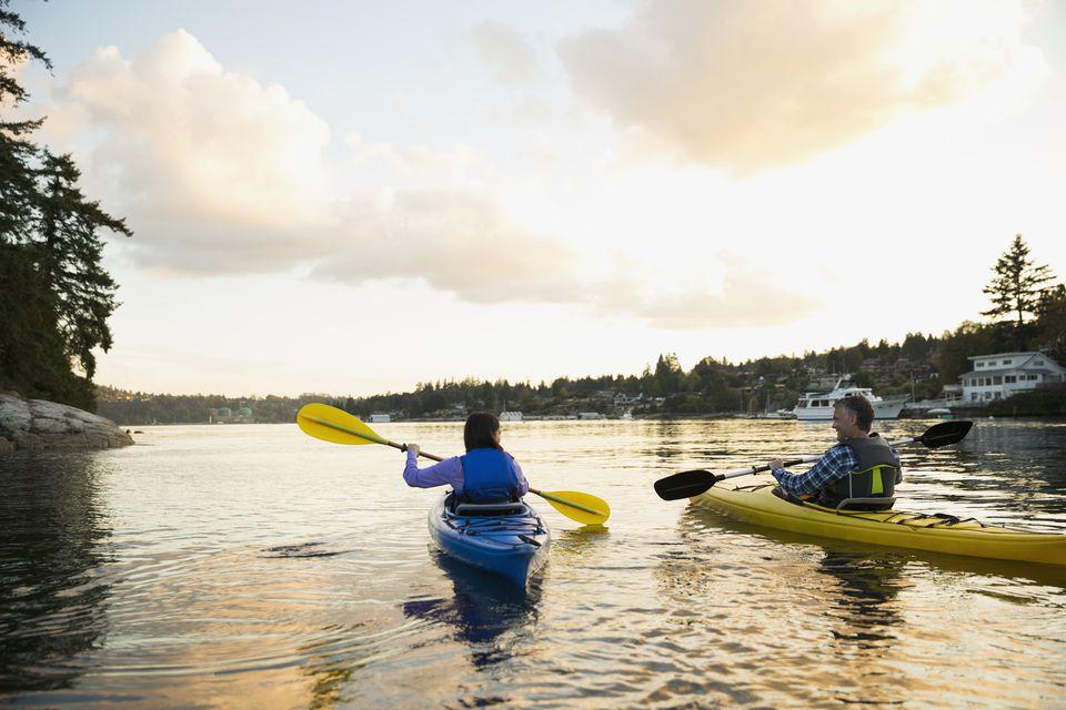 Couple kayaking on lake at sunset