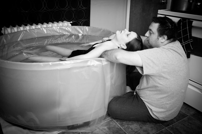 A man comforts a woman laboring in a tub