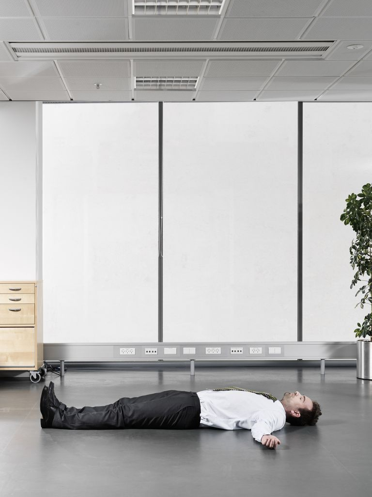 Businessman sleeping on the floor of an office.